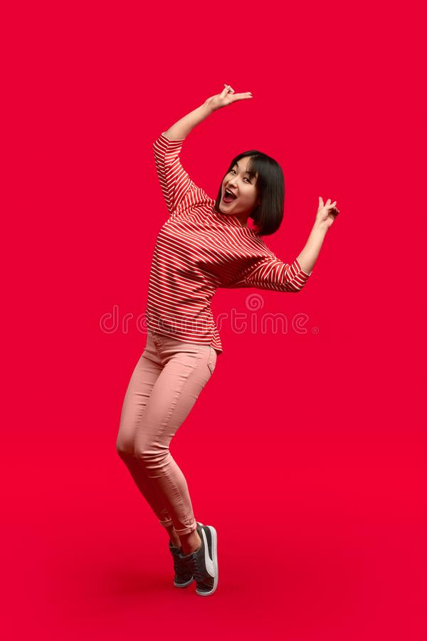 Cheerful ethnic woman standing on tiptoes and gesturing V sign stock photo