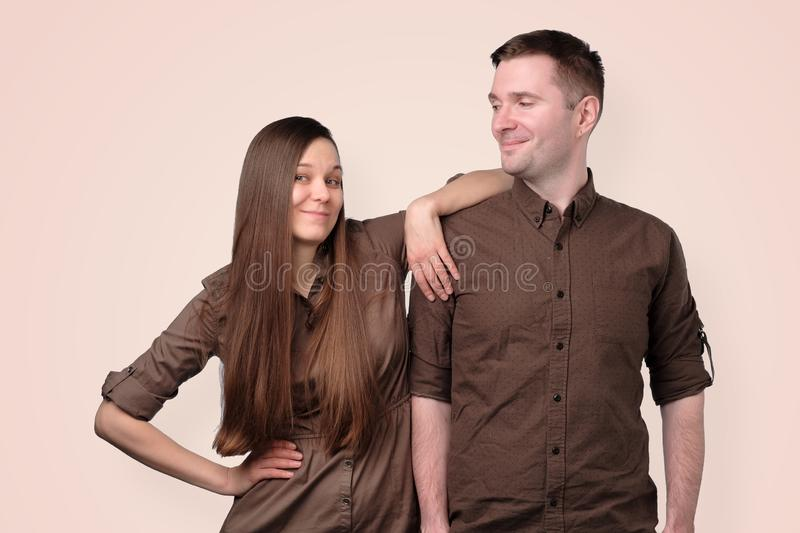 Cheerful european young couple in brown clothes stock images