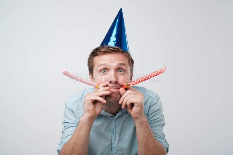 cheerful european young man having fun on party wearing blue denim shirt and holiday hat, blowing party horn stock image