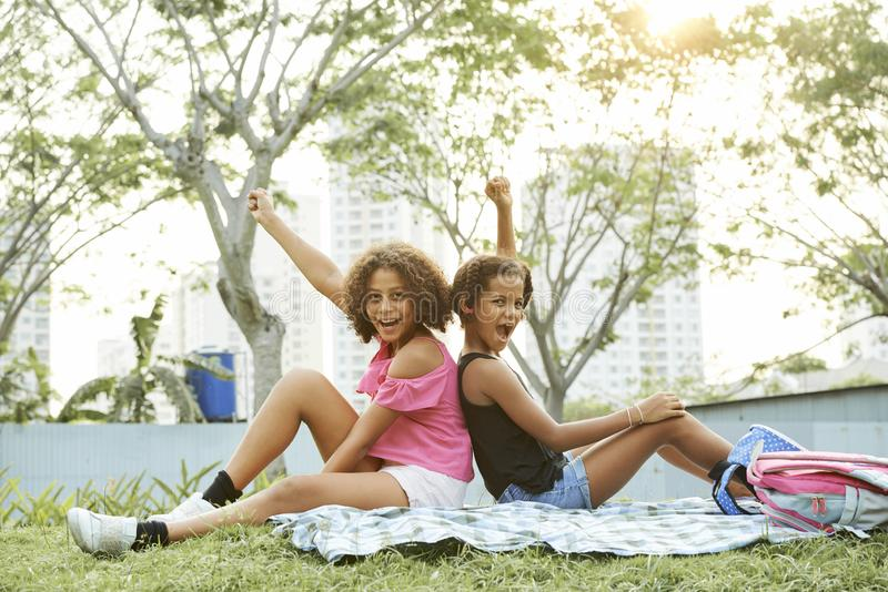 Excited black girls having fun in park stock photos