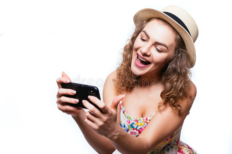 Cheerful excited girl in summer hat play games or make video call on smartphone on white background. Cheerful excited girl in cap play games or make video call royalty free stock image
