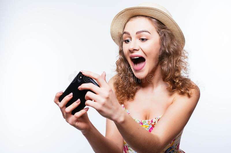 Cheerful excited girl in summer hat play games or make video call on smartphone on white background. Cheerful excited girl in cap play games or make video call stock photos