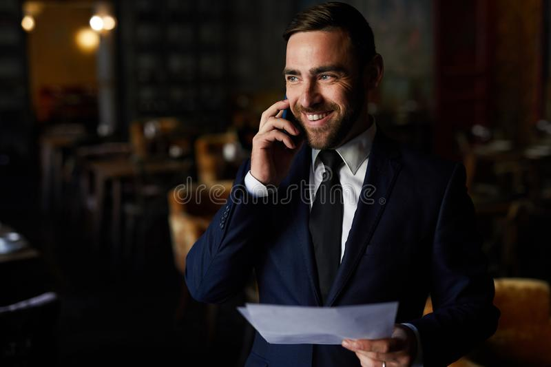 Event manager planning banquet in restaurant. Cheerful excited handsome event manager in suit checking lists and planning banquet in restaurant, he laughing and stock image