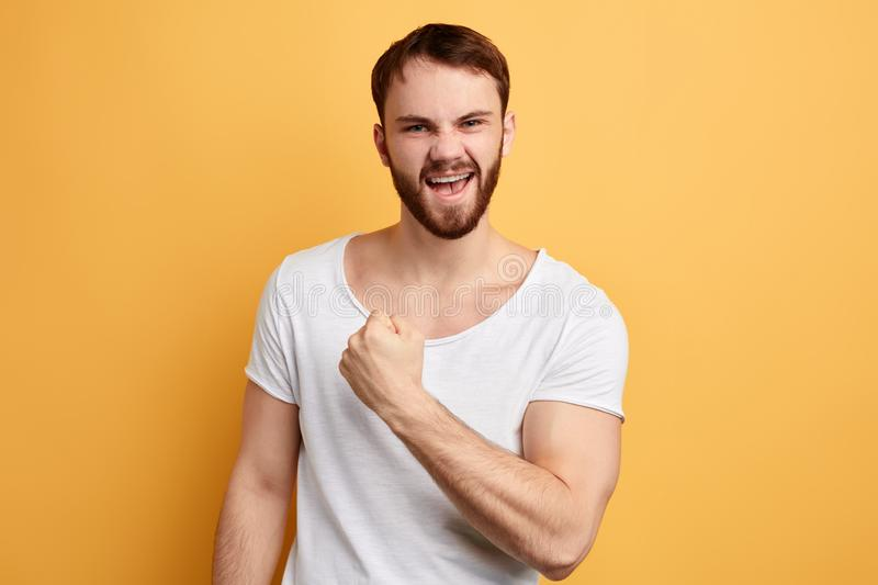 Cheerful excited happy man wearing white t-shirt celebrating victory stock photos