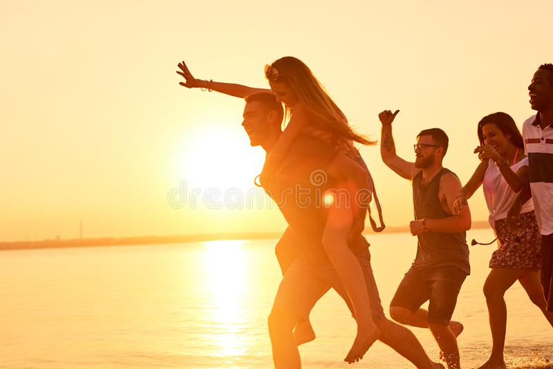 Hilarious friends running on water in light of sunset stock images