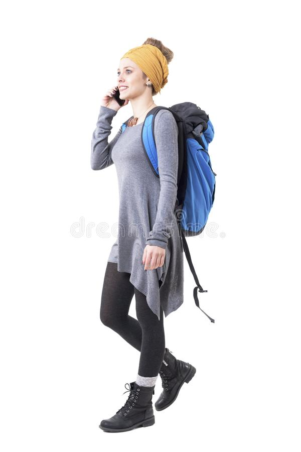 Cheerful excited young traveler woman with backpack walking and talking on the mobile phone. stock photo