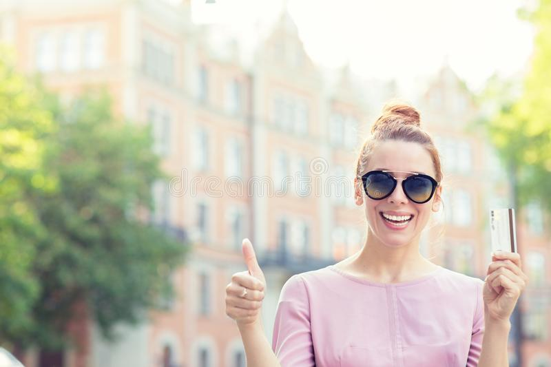 Cheerful excited young woman with credit card giving thumb up standing outdoors royalty free stock photos