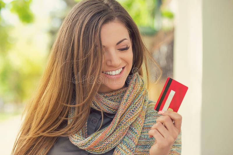 Cheerful excited young woman with credit card standing outdoors stock images
