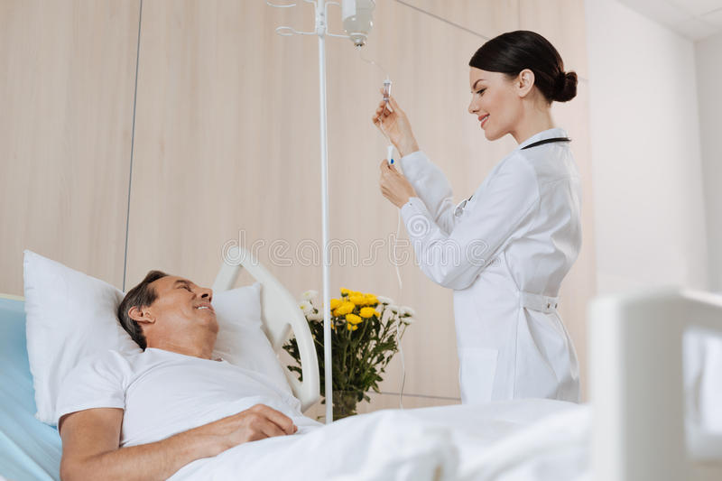 Cheerful experienced therapist interacting with her patient. Interpersonal communication. Cheerful experienced nice therapist smiling and setting up the IV while stock images