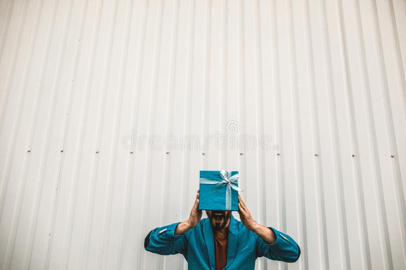 Excited man opening his mouth and showing amazing gift. Cheerful expressive young man hiding his face behind the present and opening his mouth royalty free stock image