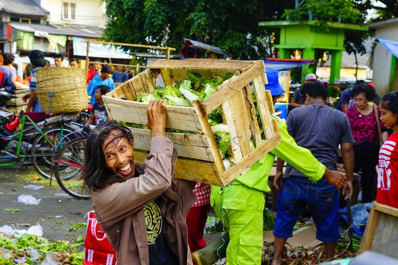A cheerful face of a vegetable stall owner. A man the owner of a vegetable stall cheerfully lifts a wooden box of vegetable sold at his stall royalty free stock photography