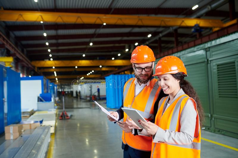 Cheerful Factory Workers. Waist up portrait of smiling female factory worker using digital tablet while discussing production with foreman in workshop, copy royalty free stock image