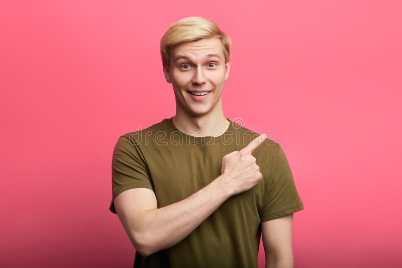 Cheerful fair-haired stylish guy pointing the finger at somewhere stock photography