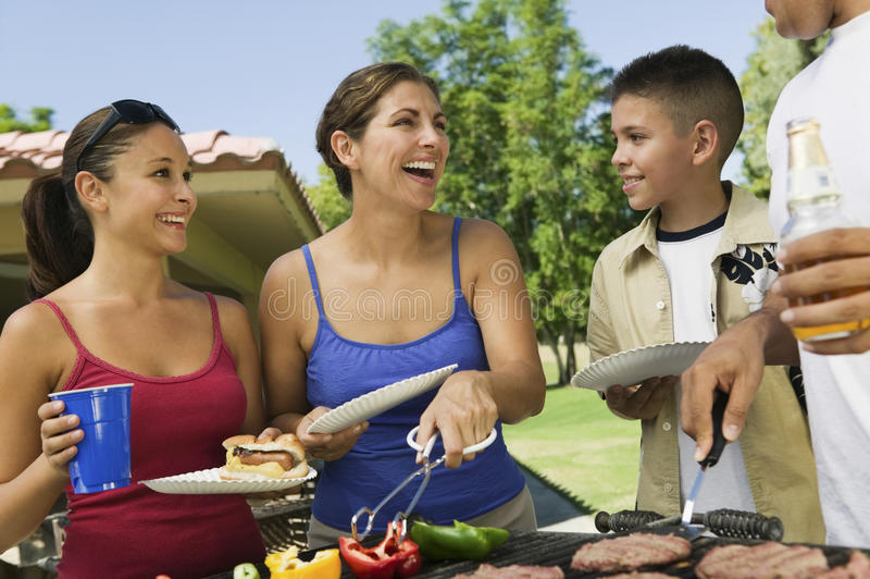 Cheerful Family Around The Grill At Picnic stock photography