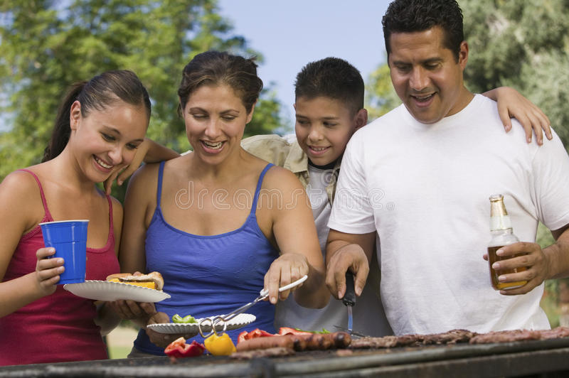 Cheerful Family Around The Grill At Picnic royalty free stock photo