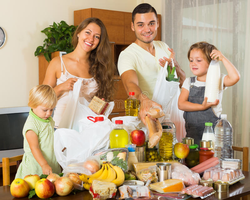 Cheerful family with bags of food. Cheerful family of four people with bags of food at home stock photo