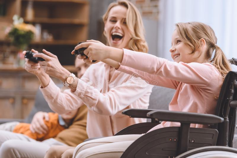 Cheerful family with disabled child in wheelchair playing with joysticks together. At home royalty free stock photo