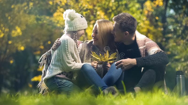 Cheerful family embracing school aged daughter in autumn park, perfect weekend royalty free stock photo