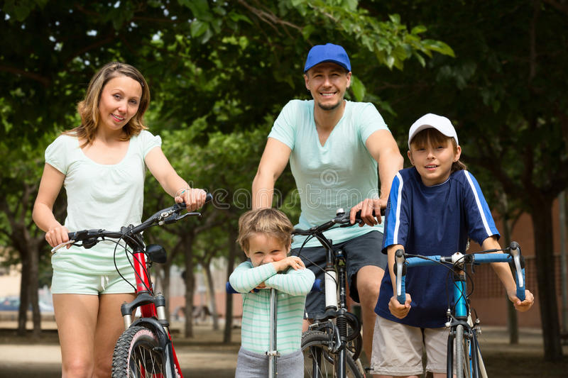 Cheerful family of four with bicycles walking stock image