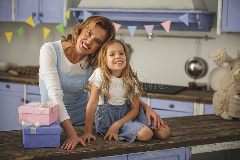 Cheerful family hanging out at home. Portrait of satisfied mother and daughter celebrating holiday in apartment. They are looking at camera while bonding to each stock photography