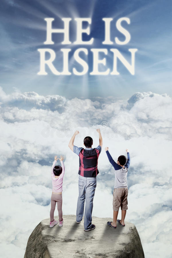 Cheerful family looking at text he is risen. Cheerful father and his children standing on the cliff while raising hands and looking at text he is risen on the royalty free stock photos