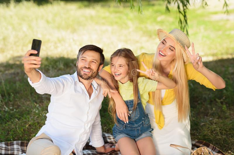 Cheerful family making selfie outdoors in park stock images
