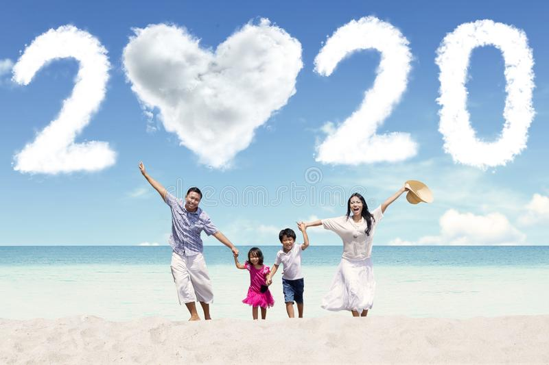 Cheerful family with number 2020 on beach stock photos