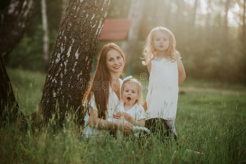 Cheerful family in a park, mom and their two lovely daughter to sit on the grass while they are looking at camera stock photos