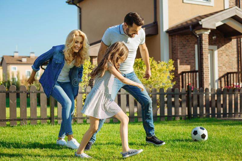 Cheerful family playing football on the backyard lawn. Energetic pastime. Upbeat happy family playing football on the green lawn in their backyard and running royalty free stock photos