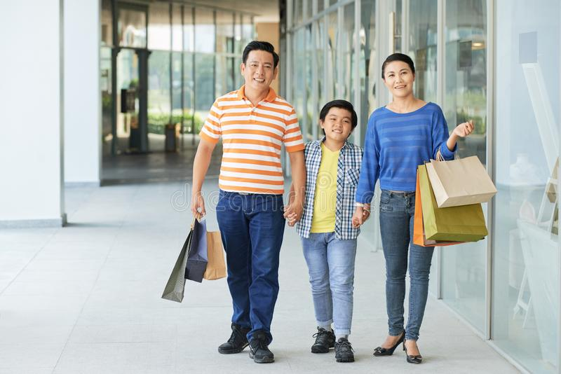 Cheerful family in shopping mall. Smiling Vietnamese family with many paper-bags walking in shopping center royalty free stock photography