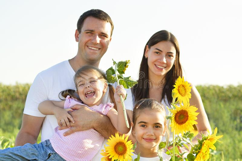 Cheerful family with sunflowers in field. Happy family of parents and two girls hugging while holding sunflowers and smiling at camera in summer field royalty free stock image