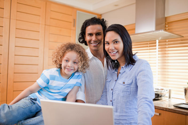 Cheerful family surfing the internet in the kitchen together. Cheerful young family surfing the internet in the kitchen together royalty free stock photos