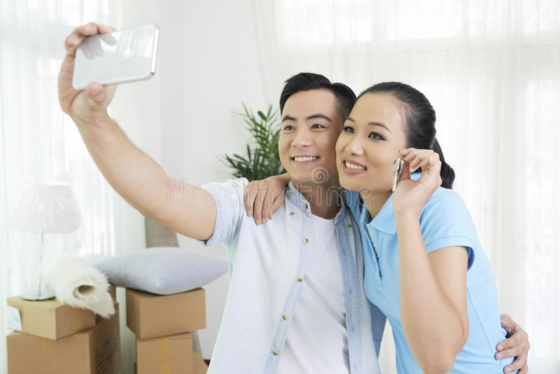 Cheerful family taking selfie. Young Vietnamese family taking selfie with keys in their new apartment stock photo