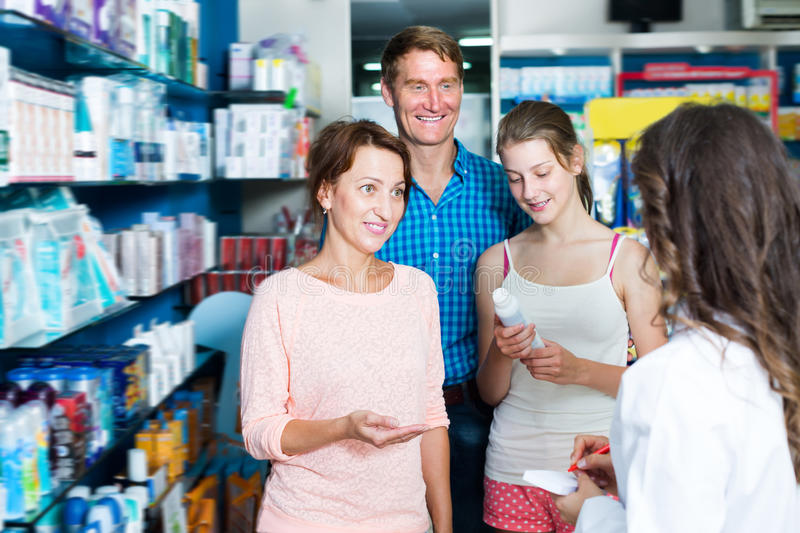 Cheerful family of three consulting druggist stock photos