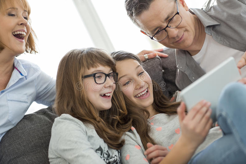 Cheerful family using tablet PC at home stock image