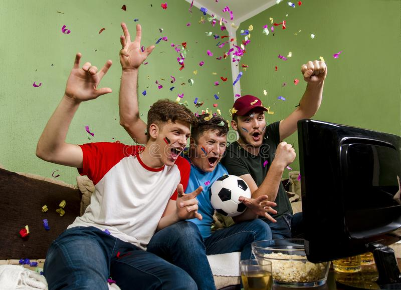 Cheerful family watching soccer cup on television stock image