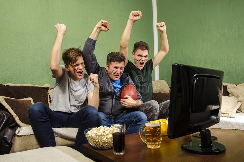 Cheerful family watching Superbowl, fist in air royalty free stock image