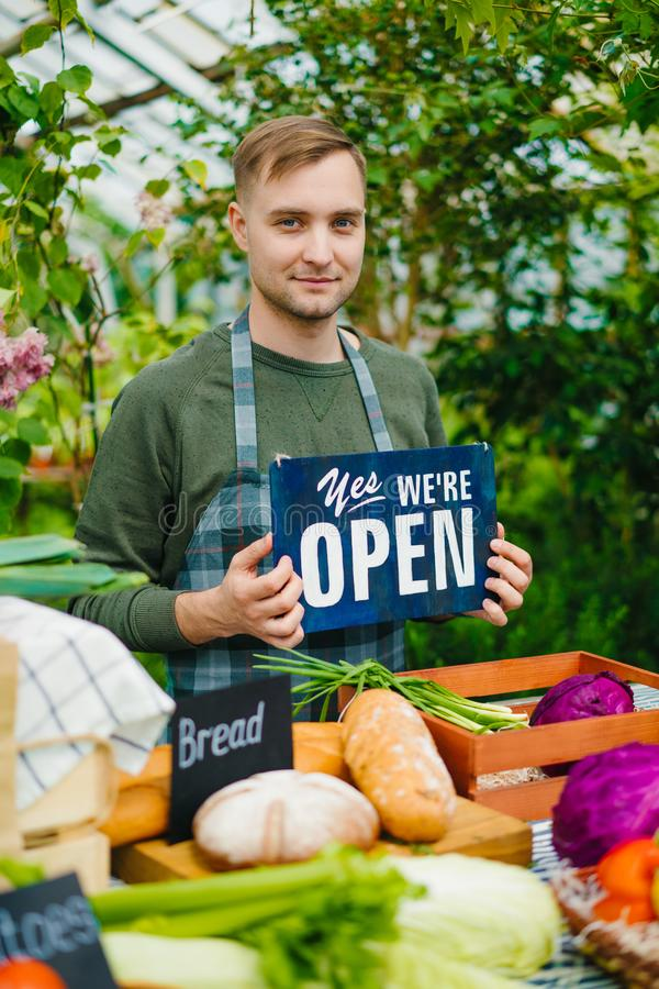 Cheerful farmer holding we are open sign in farm market selling organic food. Cheerful farmer is holding we are open sign working in farm market selling organic stock photo