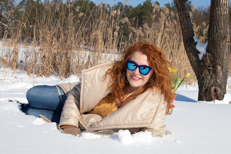 Cheerful fashionable woman resting in snow against rural environment. Full length of optimistic red haired woman in warm coat lying on snow surface and smiling royalty free stock photo