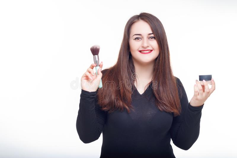 Cheerful fat brunette has fun posing with cosmetic. Plus size model, wear bodysuit in the studio with big boobs royalty free stock photo