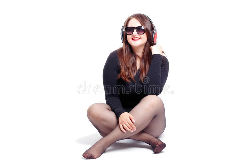 Cheerful fat brunette has fun posing with headphones. Plus size model, wear bodysuit in the studio with big boobs royalty free stock photography
