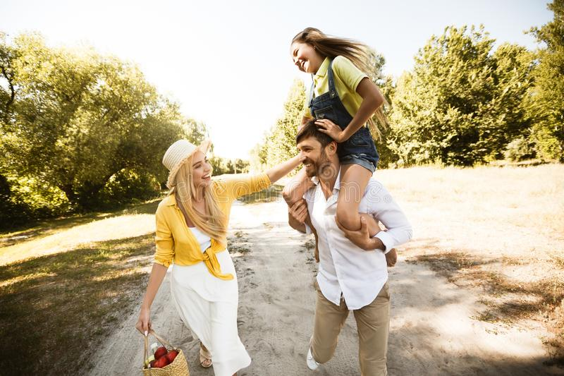Cheerful father carrying his daughter on shoulders stock image