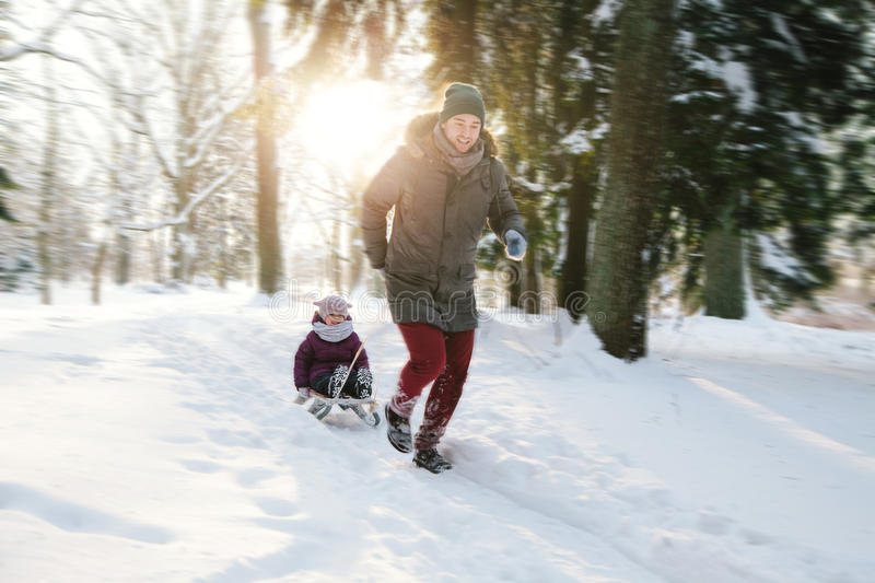 Cheerful father and daughter on a sled stock photos