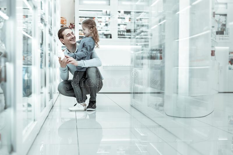 Cheerful father with his small daughter in the drugstore. stock photos