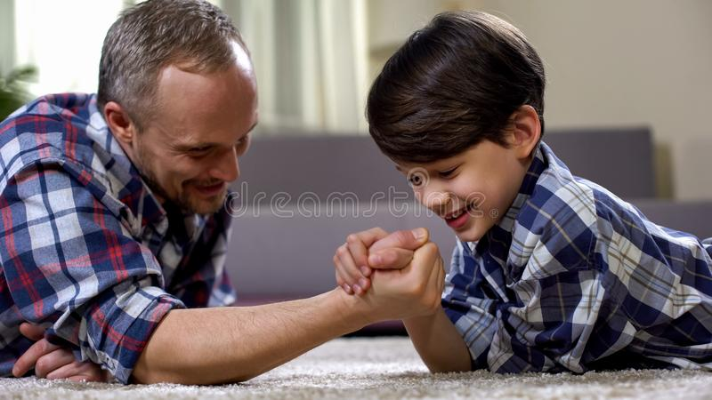Cheerful father and son arm-wrestling on floor, having fun together, rival. Stock photo royalty free stock photo