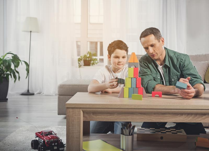 Joyful parent and kid playing at home together stock photography