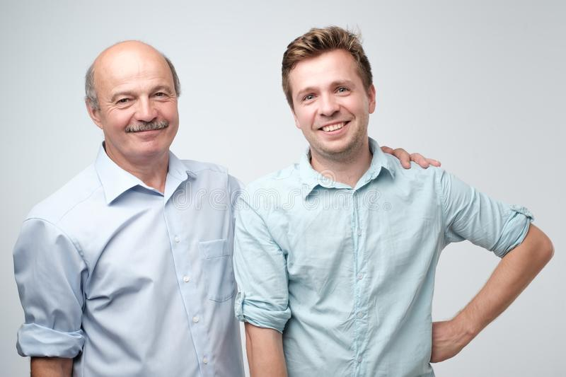 Cheerful father and son hugging and posing together stock image