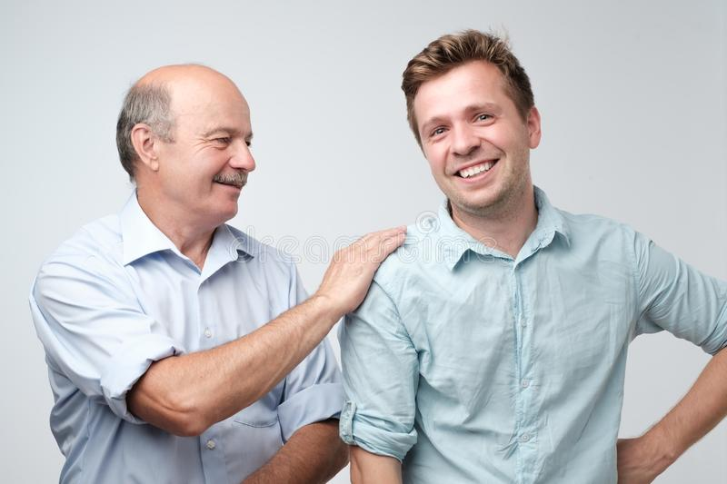 Cheerful father and son looking at each other smiling royalty free stock photos