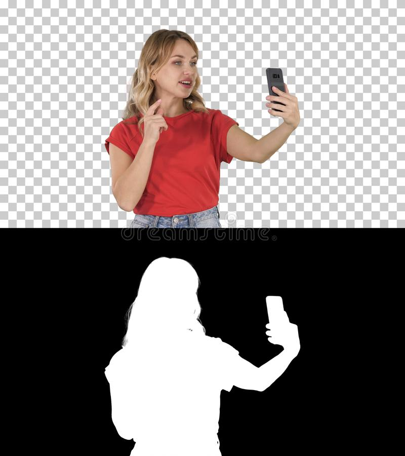 Cheerful female blogger recording video to front camera of modern telephone while walking, Alpha Channel royalty free stock image