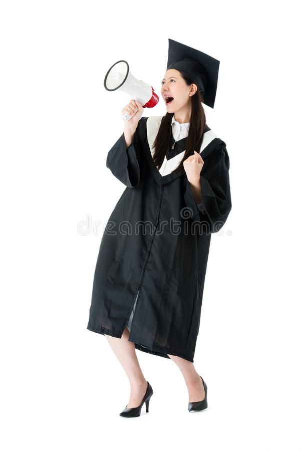 Cheerful female college student using megaphone. Cheerful young female college student using megaphone announced she getting graduation diploma and celebrating stock images